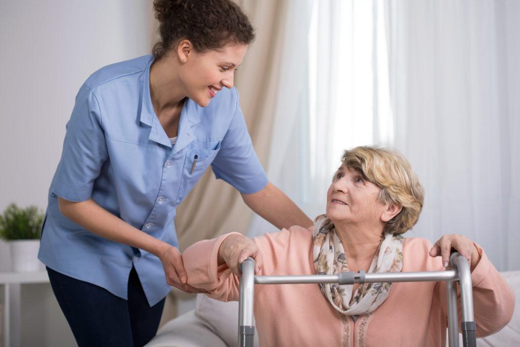 Senior woman using walking frame and supporting nurse